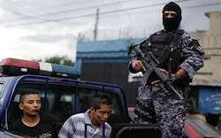 Un policía en San Salvador custodia a dos presuntos pandilleros