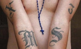 An MS-13 member in Washington displays his gang tattoos