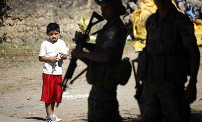 A boy looking on at police in Coban, Guatemala
