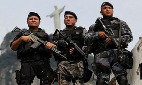Brazilian military police stand below Cristo Redentor