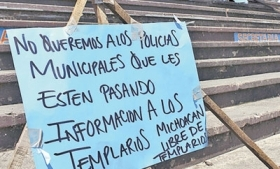 Protest sign accusing police of drug ties in Michoacan