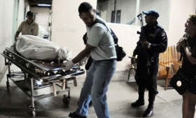Officials remove the body of a prisoner killed in the shootout