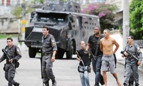 Police detain a man during disturbances in Santa Catarina