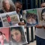 Family members hold images of Heaven victim