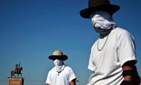 Vigilantes stand at a checkpoint in Apatzingan