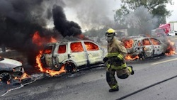 A firefighter at the site of a CJNG narco-blockade