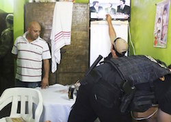 "Carlos Antonio Caballero, alias ""Capilo,"" stands as his cell is inspected"