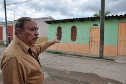 Ulises Sarmiento points at bullet holes in his house after 2009 attack