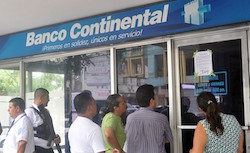 Clients gather outside a closed Banco Continental branch