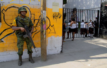 A solider stands guard at a school