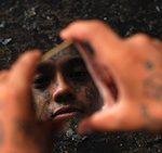An alleged Honduras gang member looking at his reflection