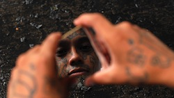 An alleged Honduras gang member looking at his reflection