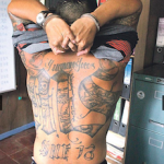 A captured MS-13 member shows his tattoos