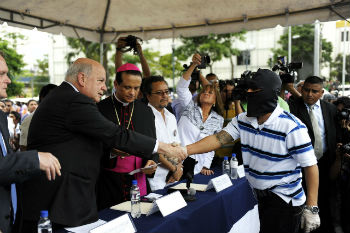 An OAS official shakes hand with a gang member as a Catholic bishop looks on