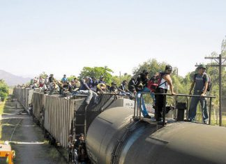 Migrants on a moving train in Mexico