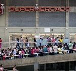 Venezuelans lining up in front of a supermarket