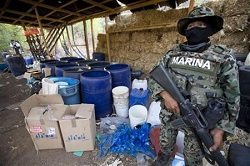 A Mexican soldier stands guards in front of a seized synthetic drug lab in Sinaloa.