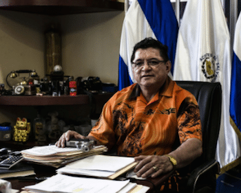 Catalino Mirando, owner of Acostes bus company, poses with his 9 mm pistol in his office.