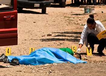 Forensic experts examine a body on a beach