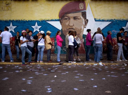Crowds hold up a picture of President Hugo Chavez