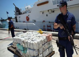 Authorities guard a cocaine shipment seized in Caribbean waters