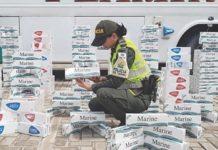 Agente de policía colombiana examina cajas de cigarrillos de contrabando